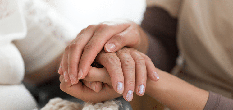 Caregiver holding patients hand